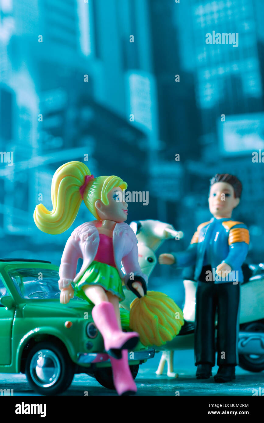 Male and female toy figures standing beside parked vehicles - Stock Image