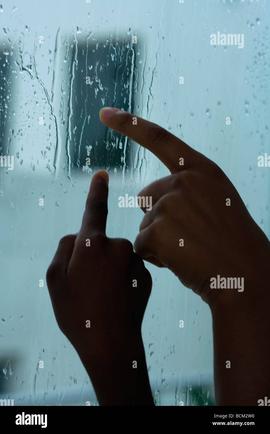Parent and child tracing raindrops on window with fingers, cropped view of hands - Stock Image