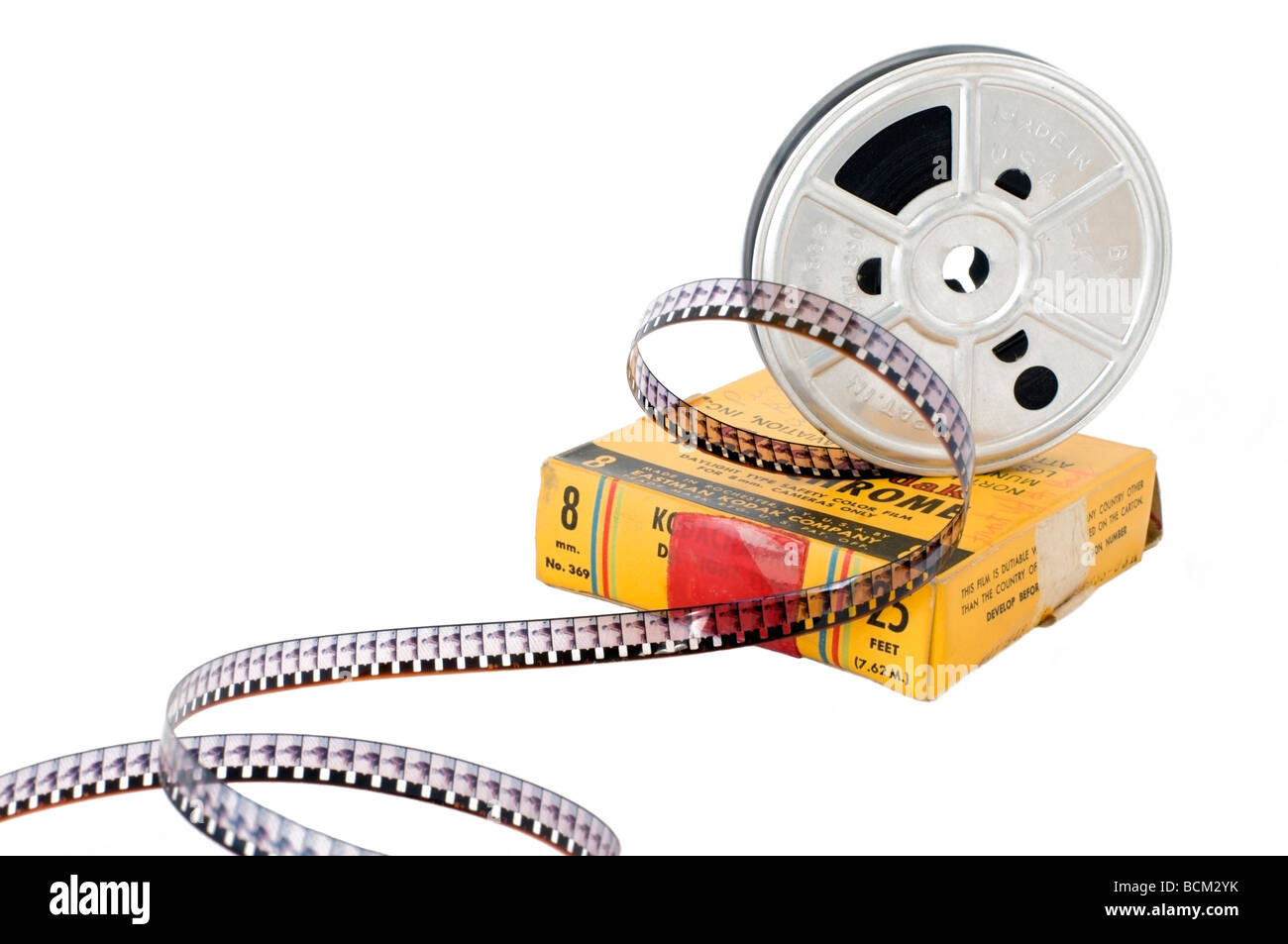 An old 8mm Kodachrome colour movie film reel with film unrolled perched on top of the original yellow film box. - Stock Image