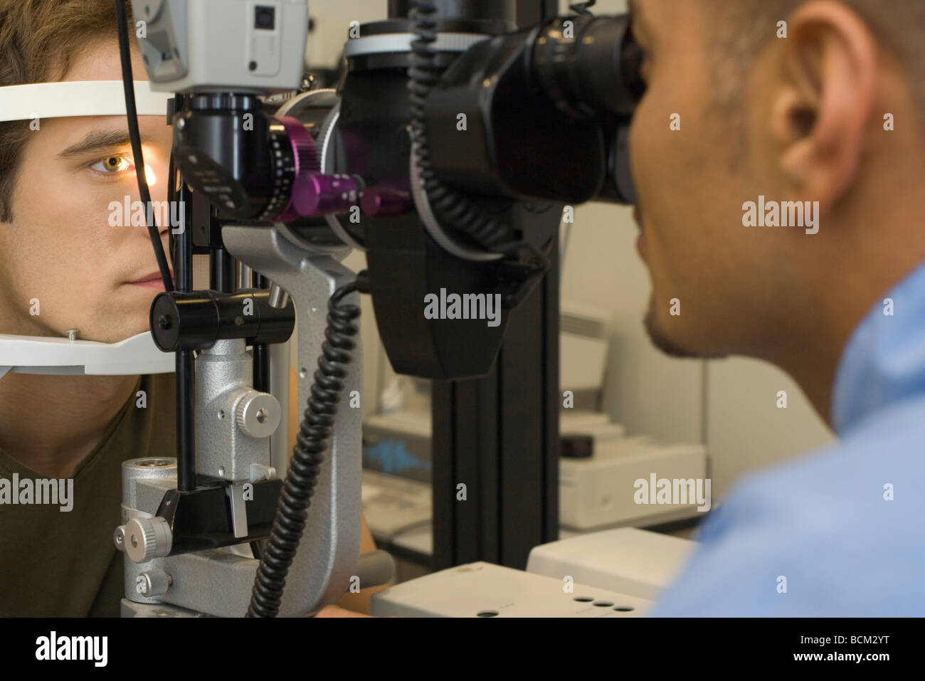 Ophthalmologist examining patient's eyes with tonometer - Stock Image