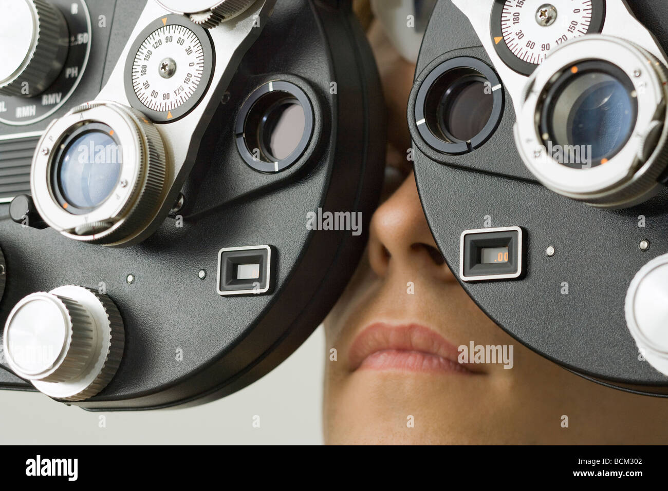 Patient looking into phoropter at eye doctor's office, extreme close-up - Stock Image