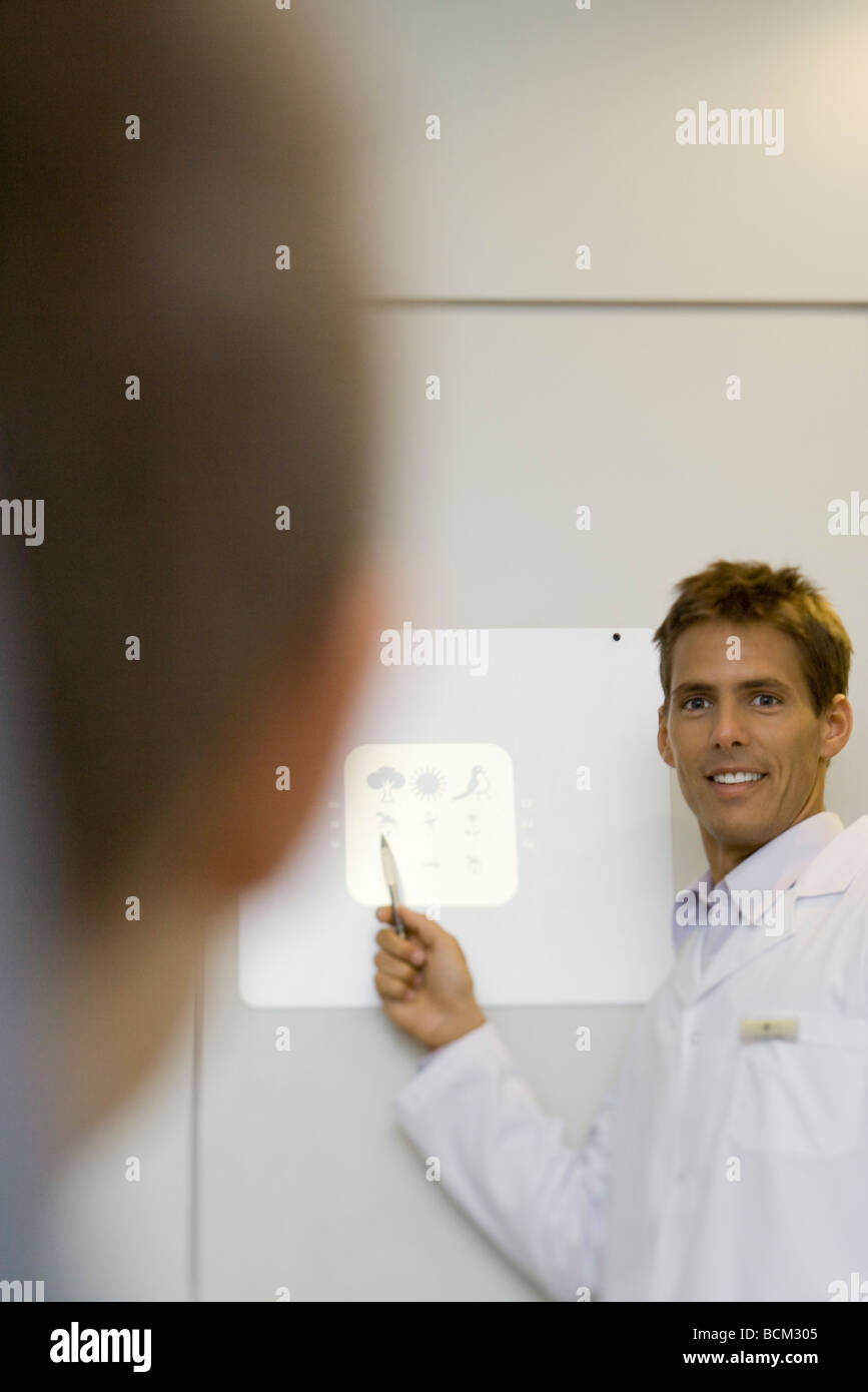 Doctor giving patient vision test, focus on background - Stock Image