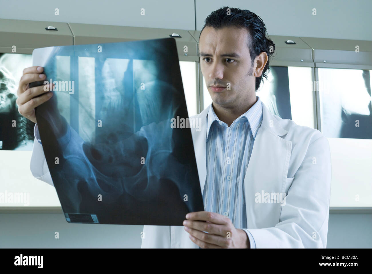 Young doctor looking at x-ray - Stock Image