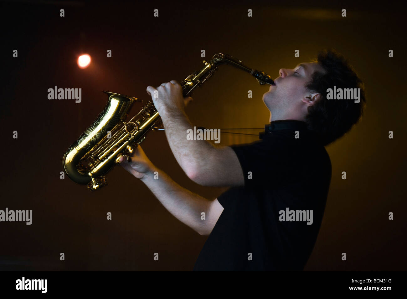 Young man playing saxophone in night club, side view - Stock Image