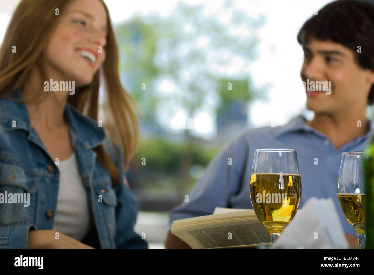 Friends laughing in outdoor cafe, glasses of beer in foreground - Stock Image