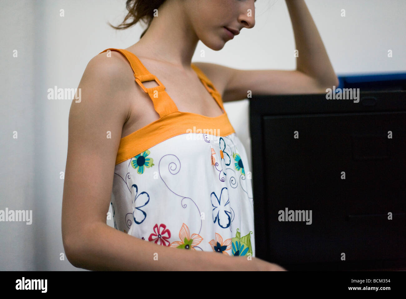 Young woman in tank top leaning against filing cabinet, cropped - Stock Image