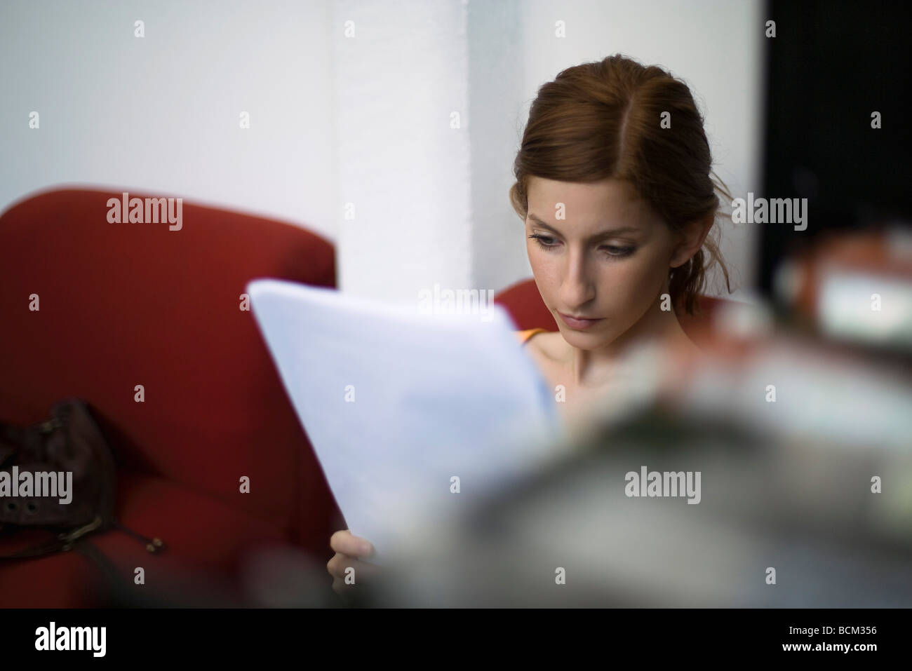 Young woman reading document - Stock Image