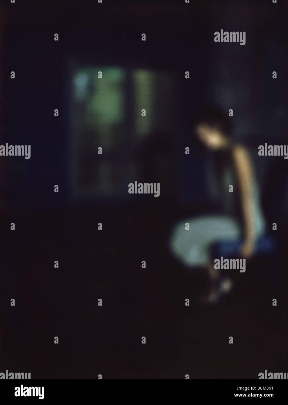 Woman sitting in dark room, defocused - Stock Image