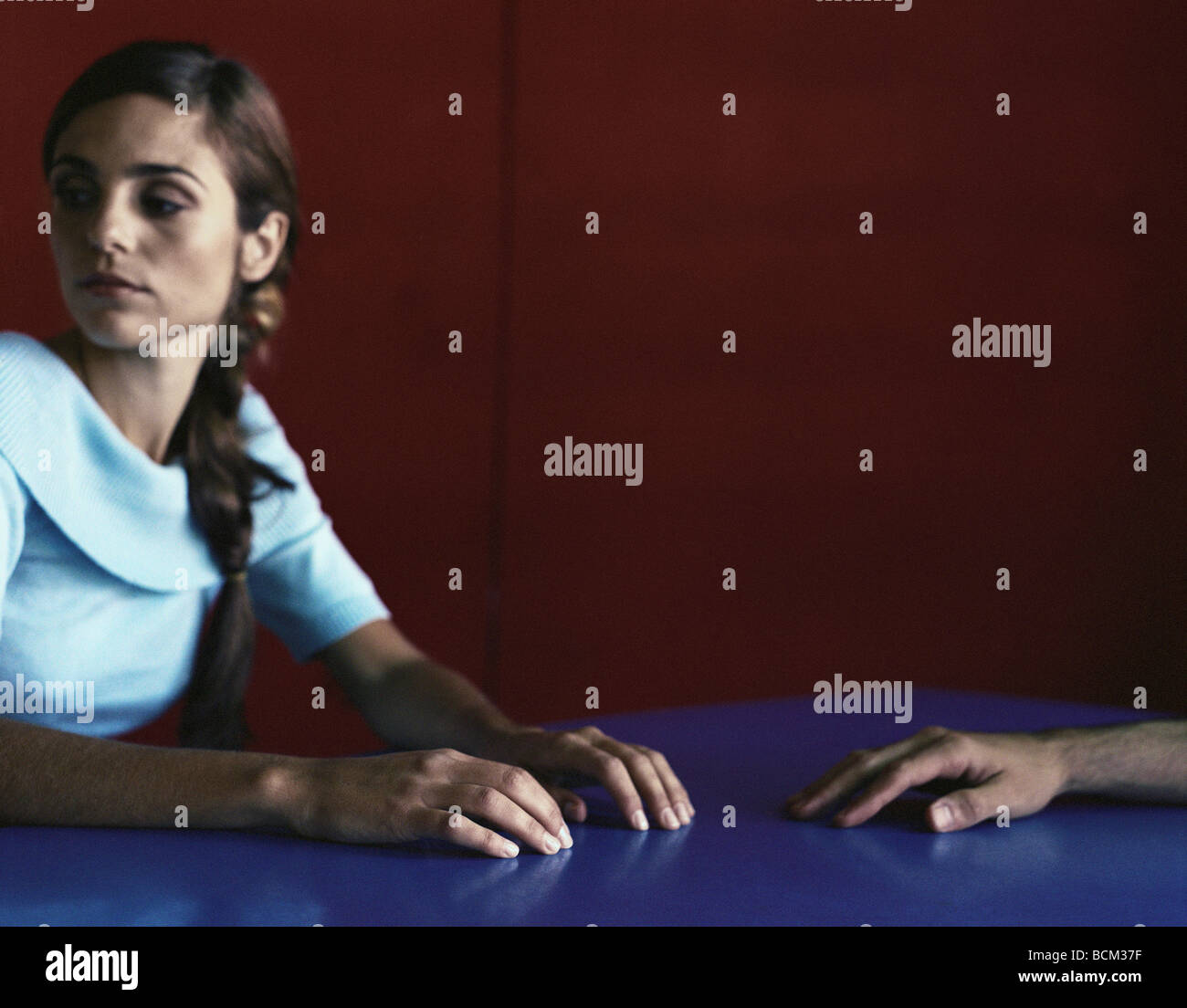 Woman and man sitting at table, woman looking away, cropped - Stock Image
