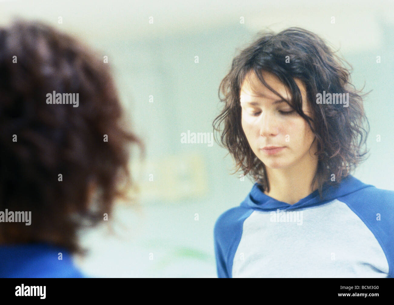 Young woman standing in front of mirror with eyes closed Stock Photo