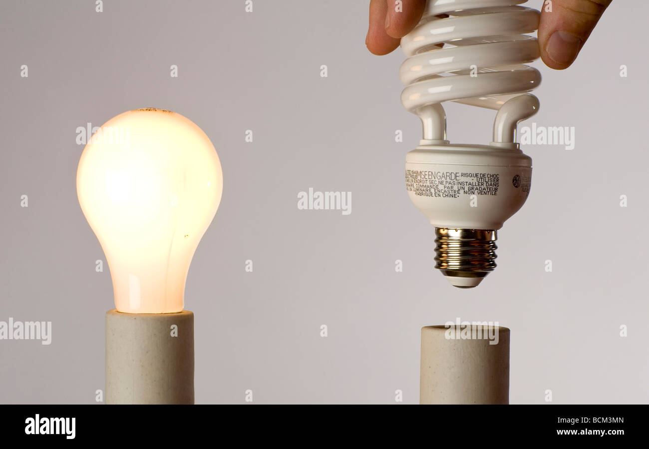 Replacing lightbulbs with Energy Efficient Compact fluorescent bulbs - Stock Image