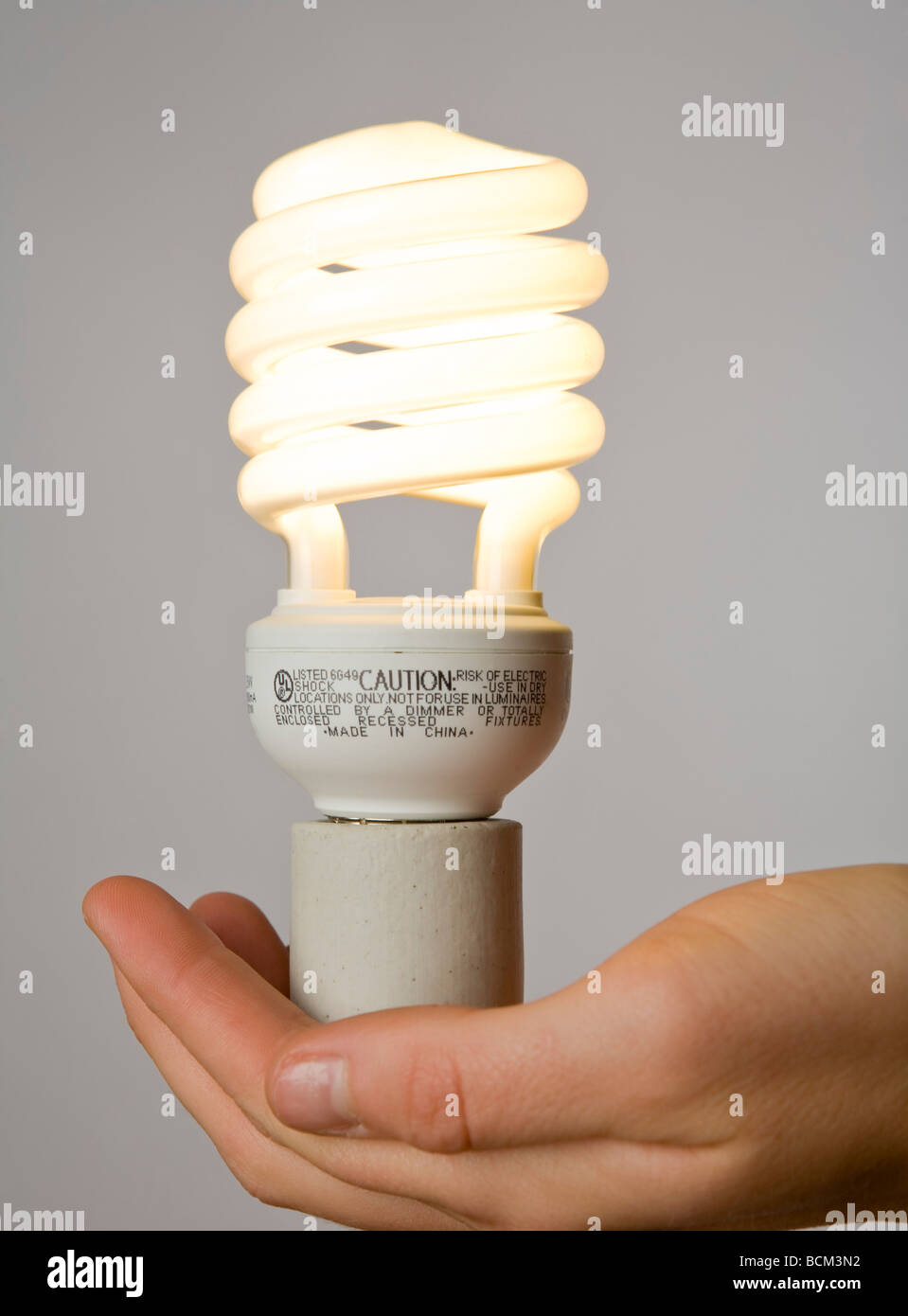 Hand holding a new Energy efficient Compact fluorescent lightbulb - Stock Image