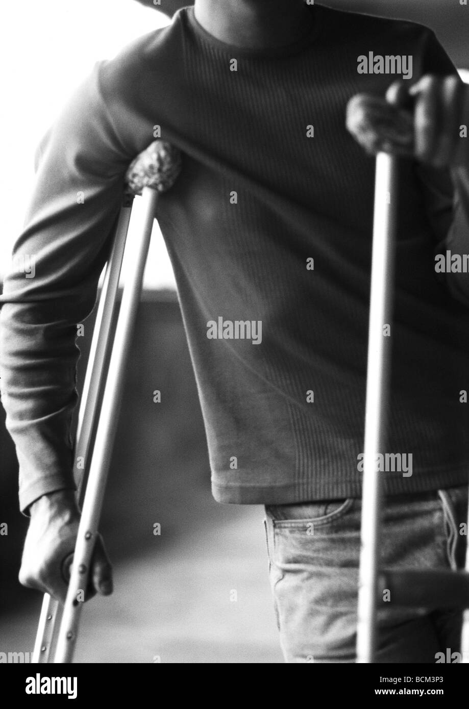 Man using crutches - Stock Image