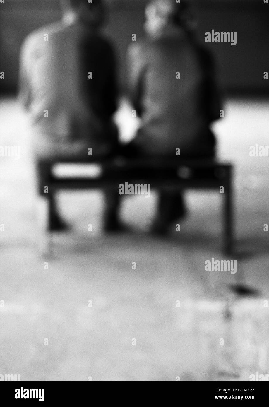 Man and woman sitting on bench, talking, rear view, defocused - Stock Image