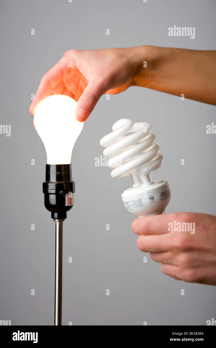 Replacing an old lightbulb with an Energy Efficient Compact Fluorescent bulb - Stock Image