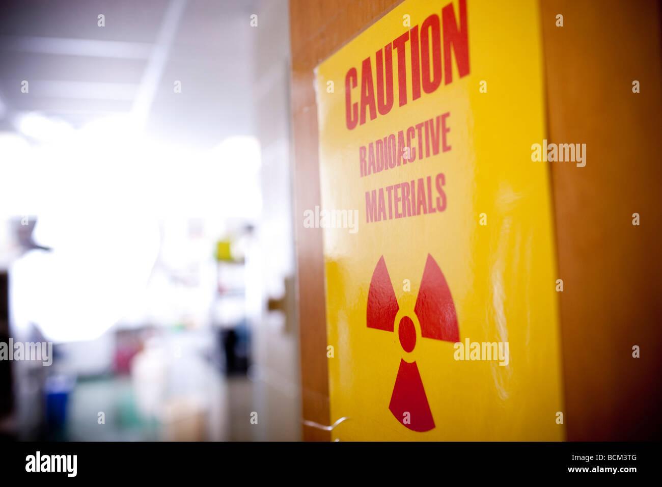 Caution Radioactive Materials sign on classroom doorway - Stock Image