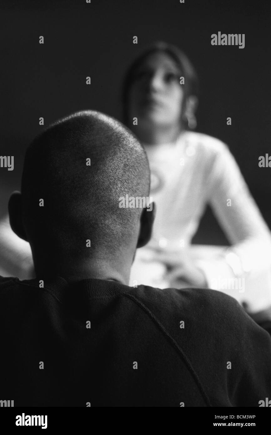 Two people face to face, focus on man with shaved head in foreground - Stock Image
