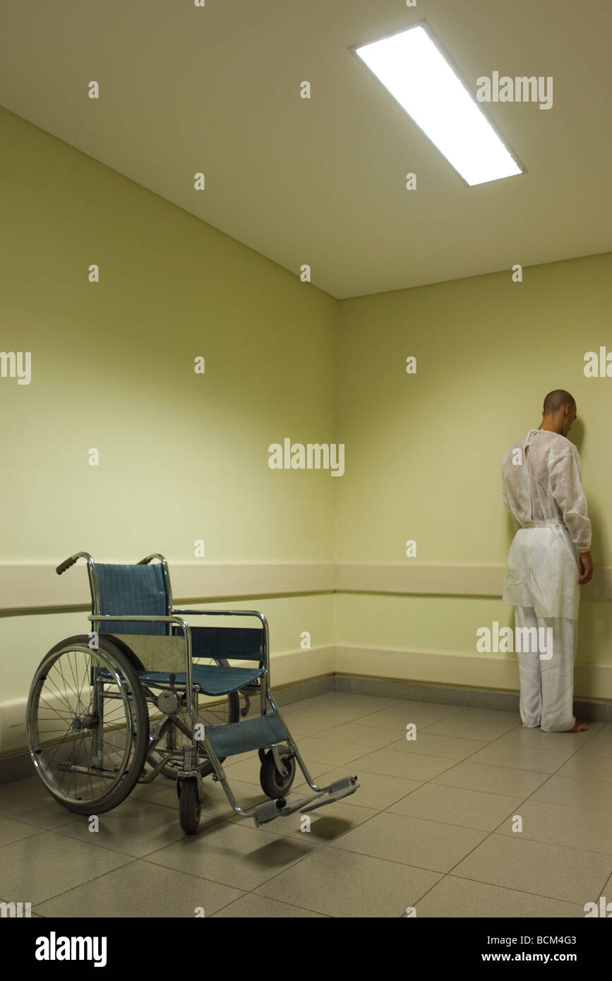 Male patient facing wall, wheelchair in foreground - Stock Image