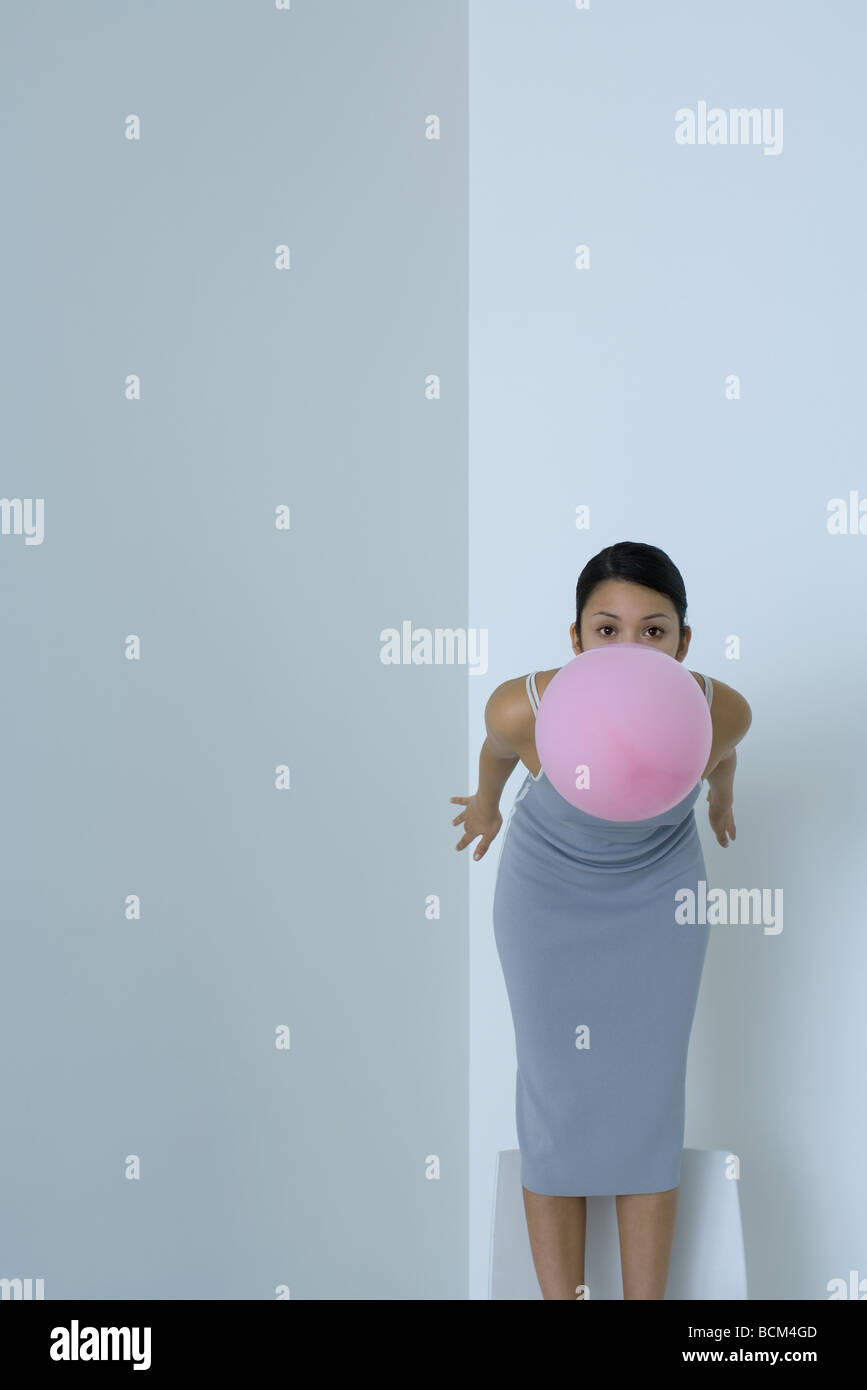 Woman bending over, holding balloon in mouth, looking at camera - Stock Image