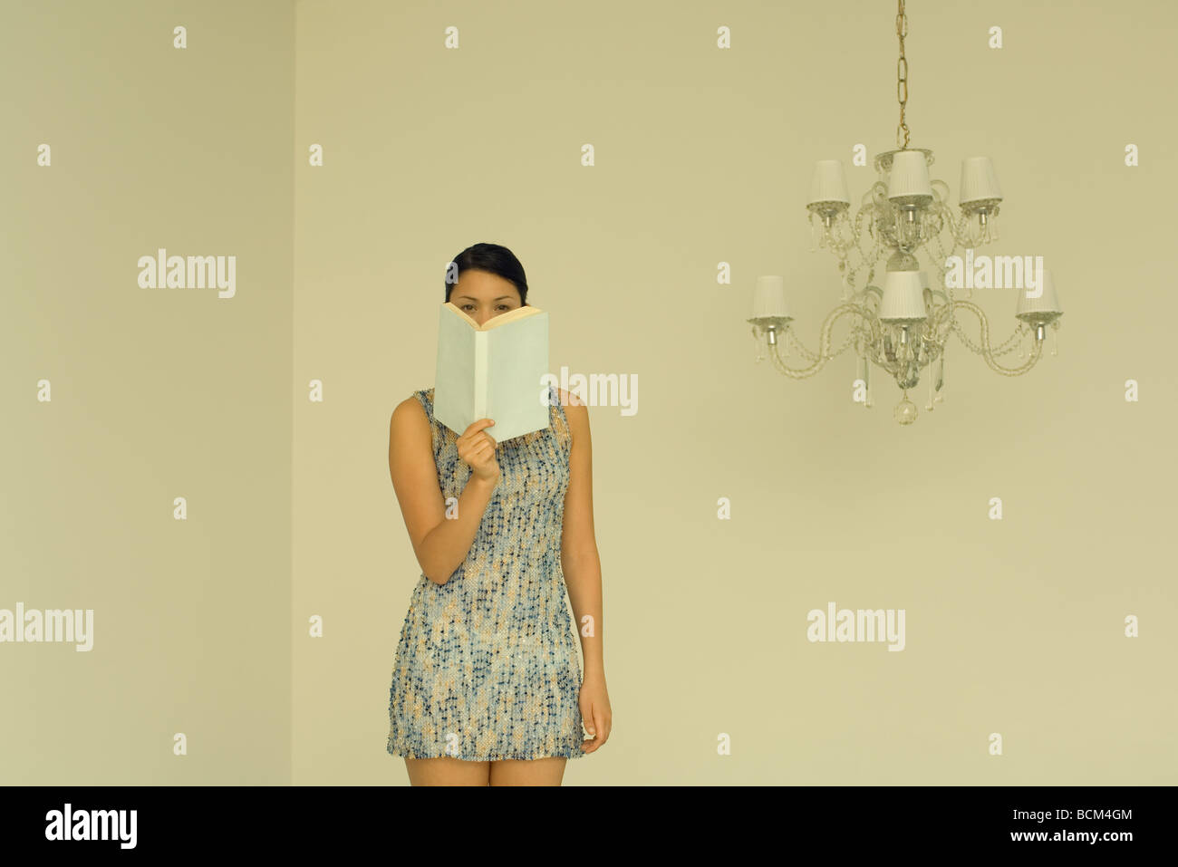 Woman standing beside chandelier, peeking over book at camera - Stock Image