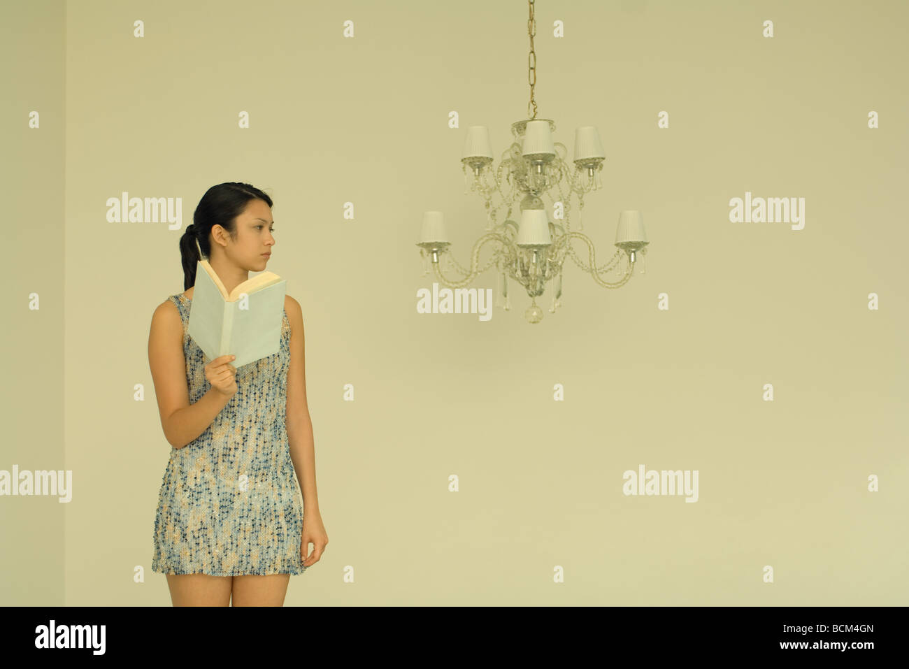 Woman holding book, frowning in direction of unlit chandelier - Stock Image