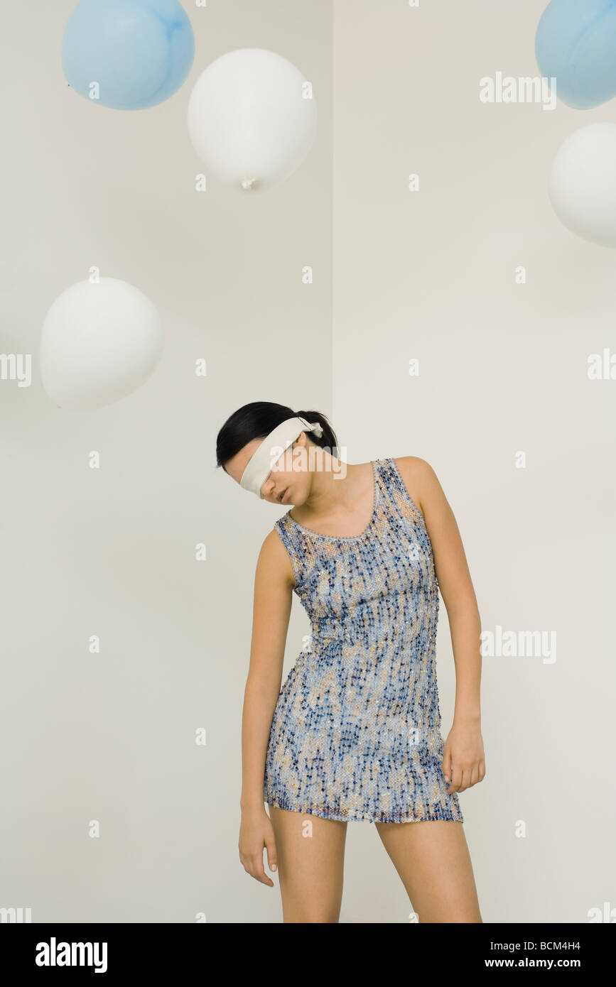 Woman blindfolded, head down, balloons floating overhead - Stock Image