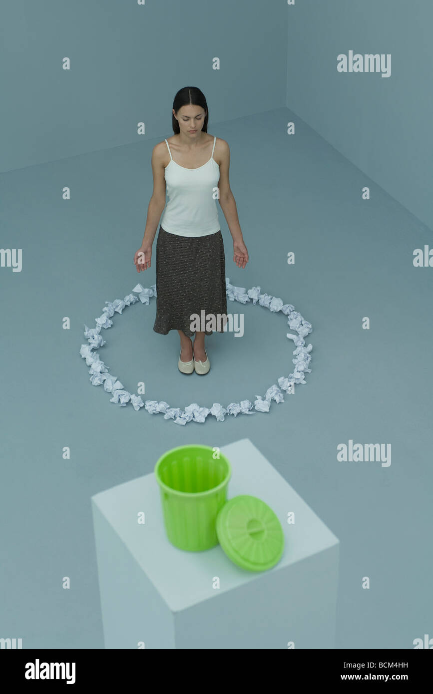 Woman standing inside circle of paper balls, eyes closed, garbage can in foreground - Stock Image