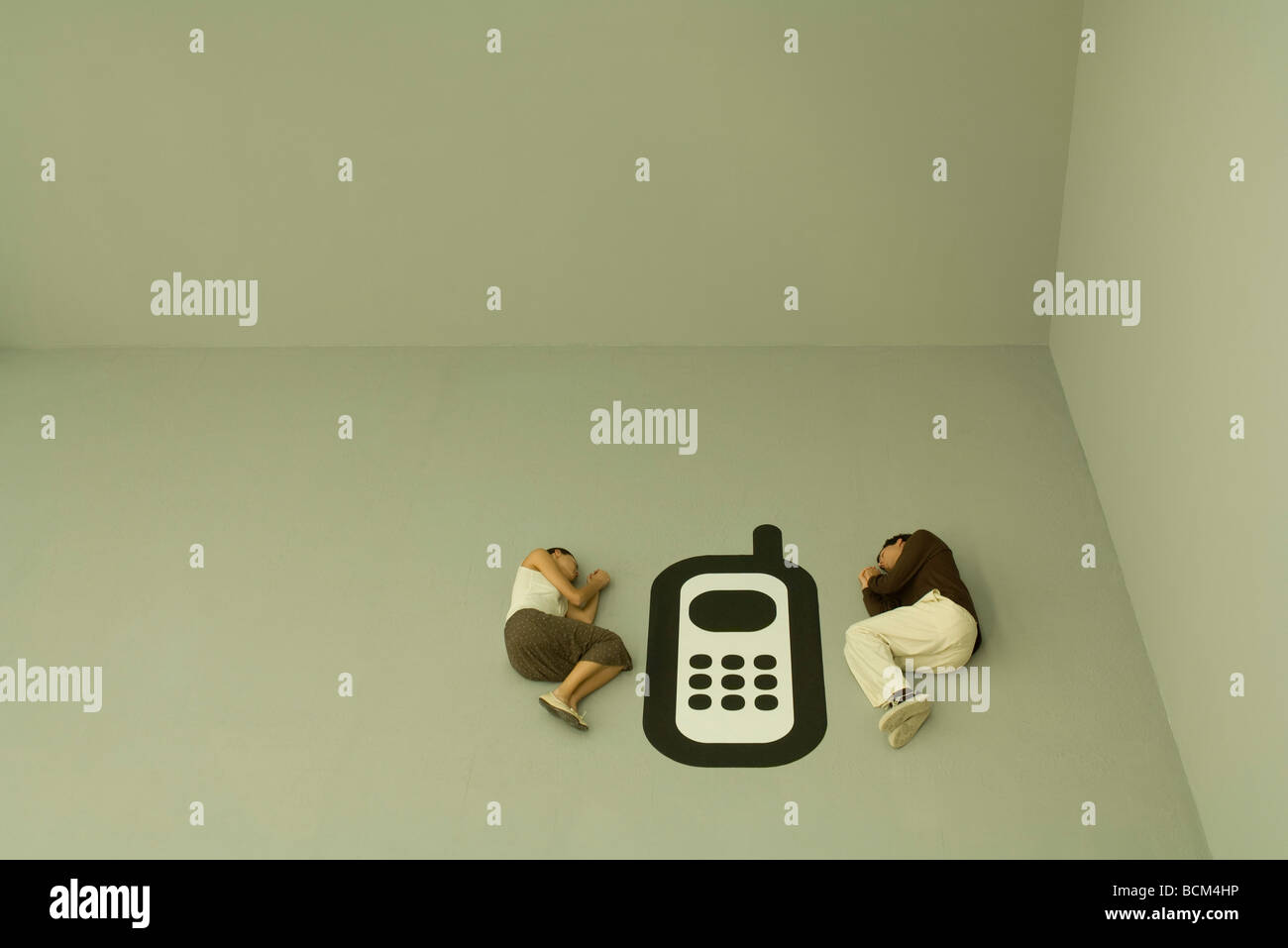 Man and woman lying down on the ground with large cell phone graphic between them - Stock Image
