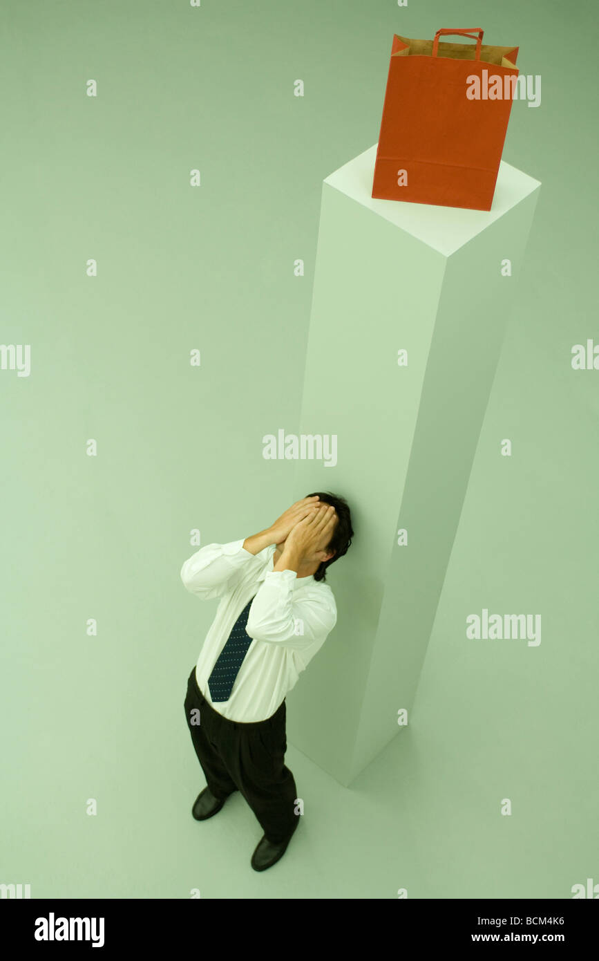 Man leaning against tall pedestal with shopping bag on top, hands over face - Stock Image