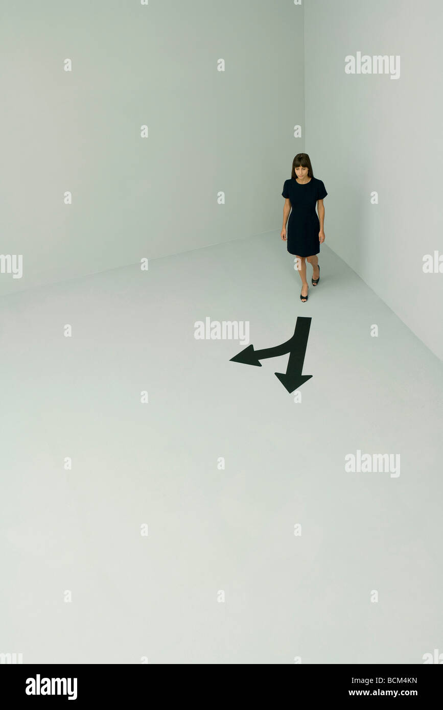 Woman walking, arrows pointing different directions, high angle view - Stock Image