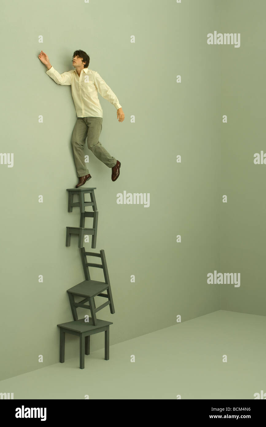Man standing on top of stacked chairs and tables, one arm raised ...
