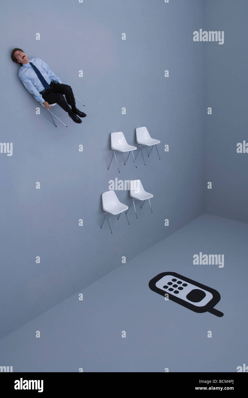 Group of chairs arranged before large cell phone, man flying away in one chair - Stock Image