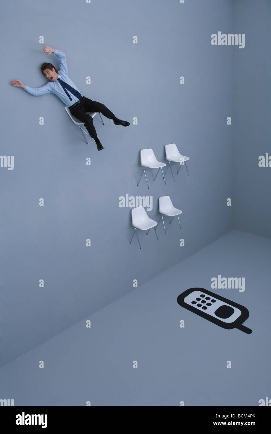 Man sitting in chair, falling towards other chairs arranged before large cell phone - Stock Image