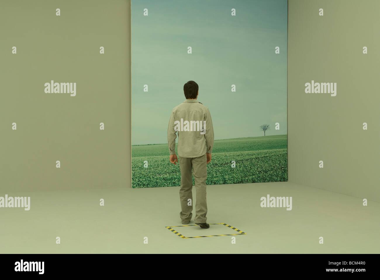 Man stepping toward large photograph of rural scene, hazard tape on the floor around him - Stock Image