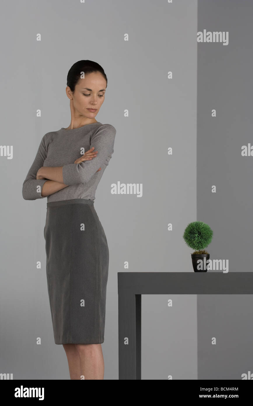 Woman standing beside table with arms folded, looking over shoulder at potted plant - Stock Image