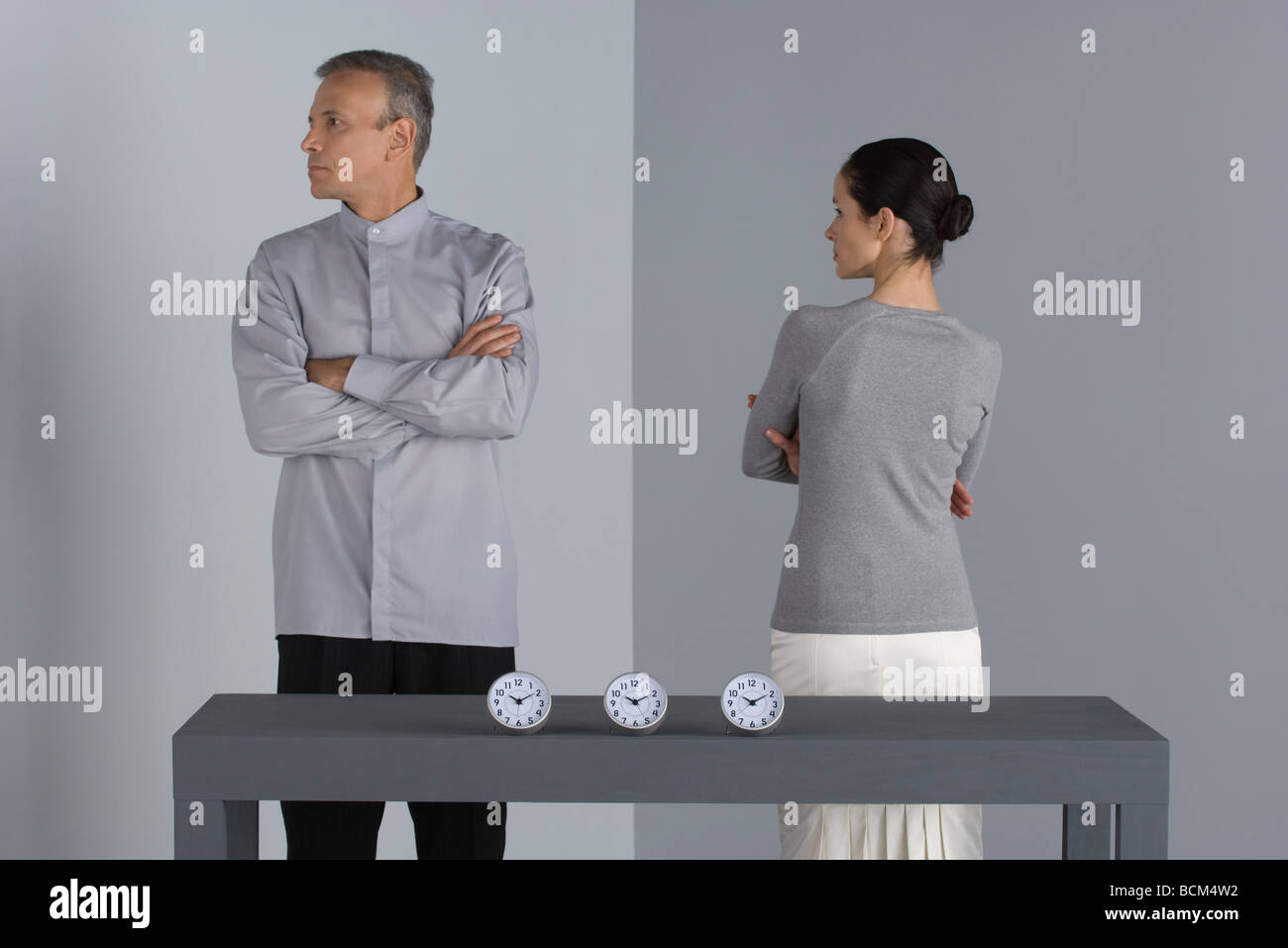 Couple standing with arms folded, backs turned to each other, clocks on table in front of them - Stock Image