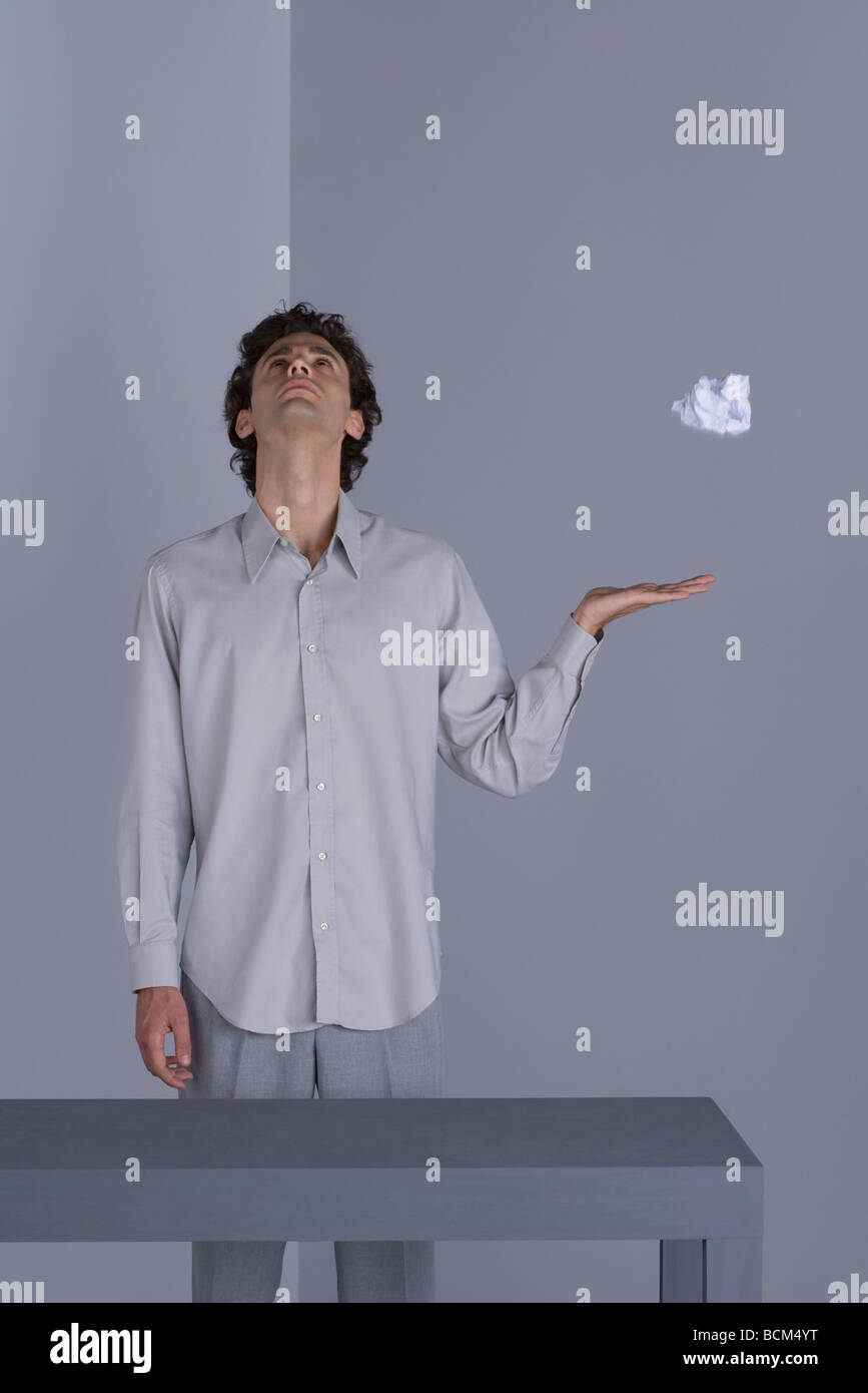 Man holding hand beneath paper ball floating mid-air, looking up - Stock Image