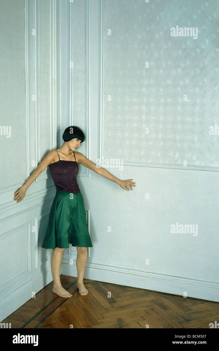 Woman in skirt and bustier standing in corner, arms out - Stock Image