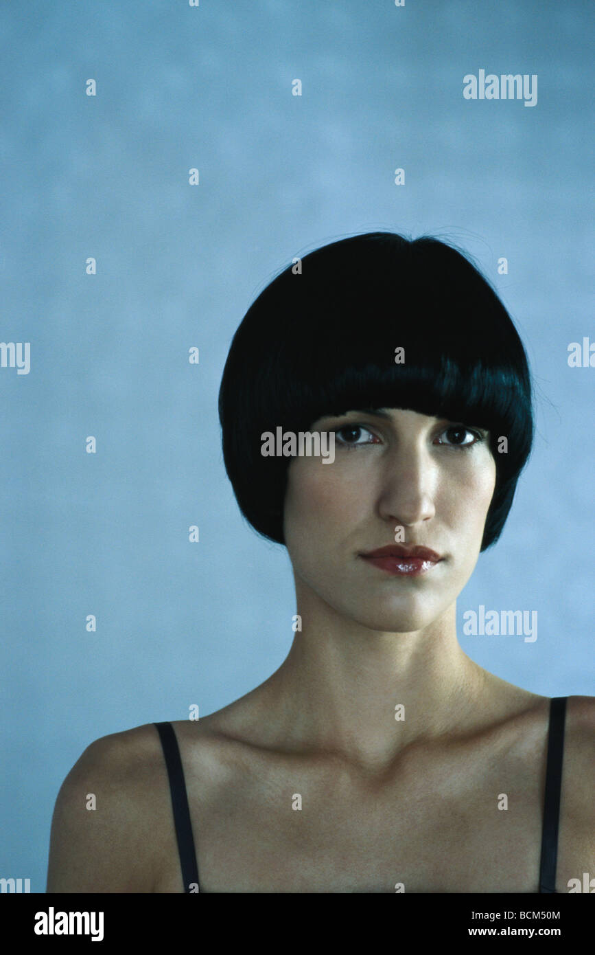 Woman with black hair looking at camera, portrait - Stock Image