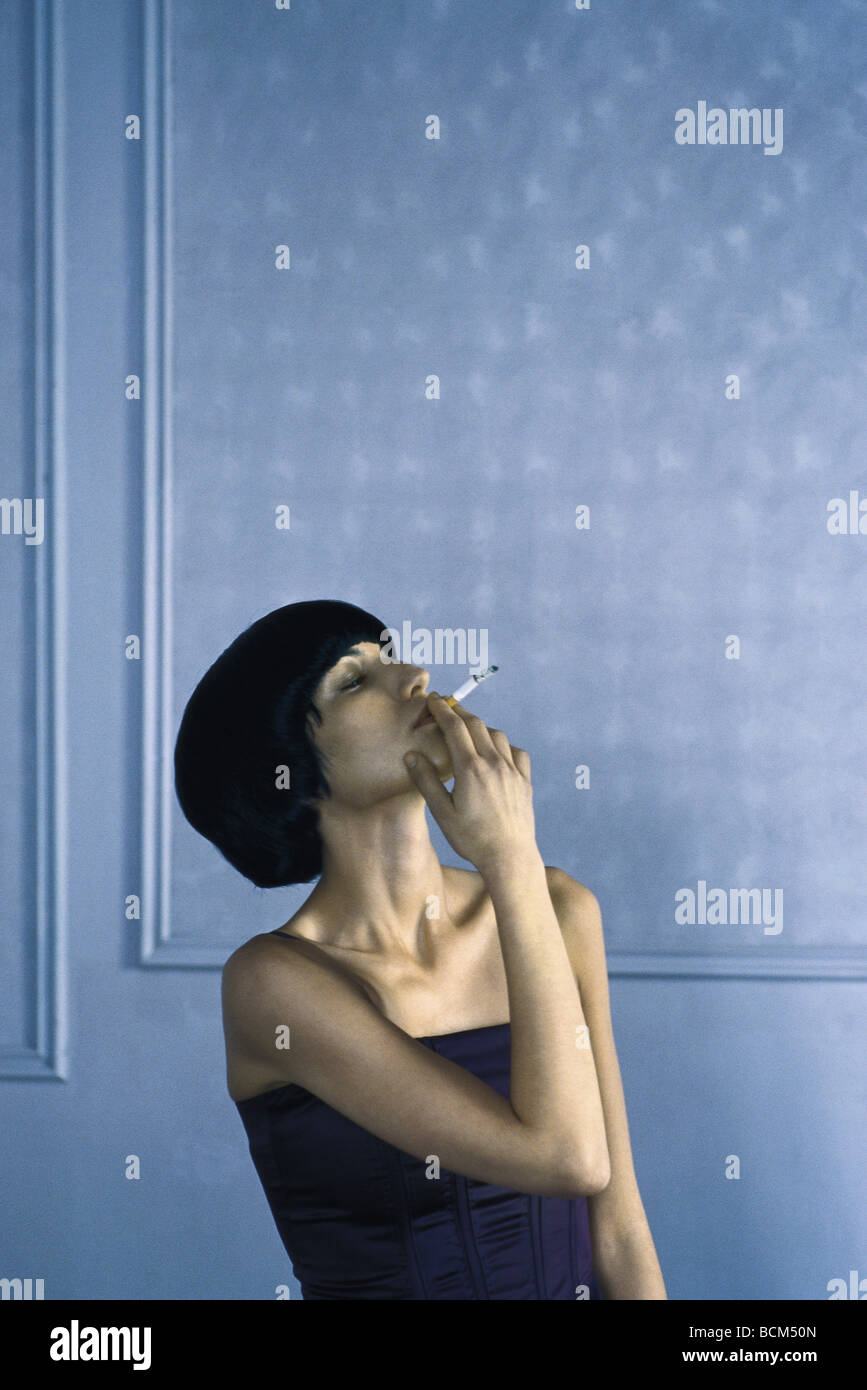 Woman smoking cigarette, head back, eyes half-opened - Stock Image