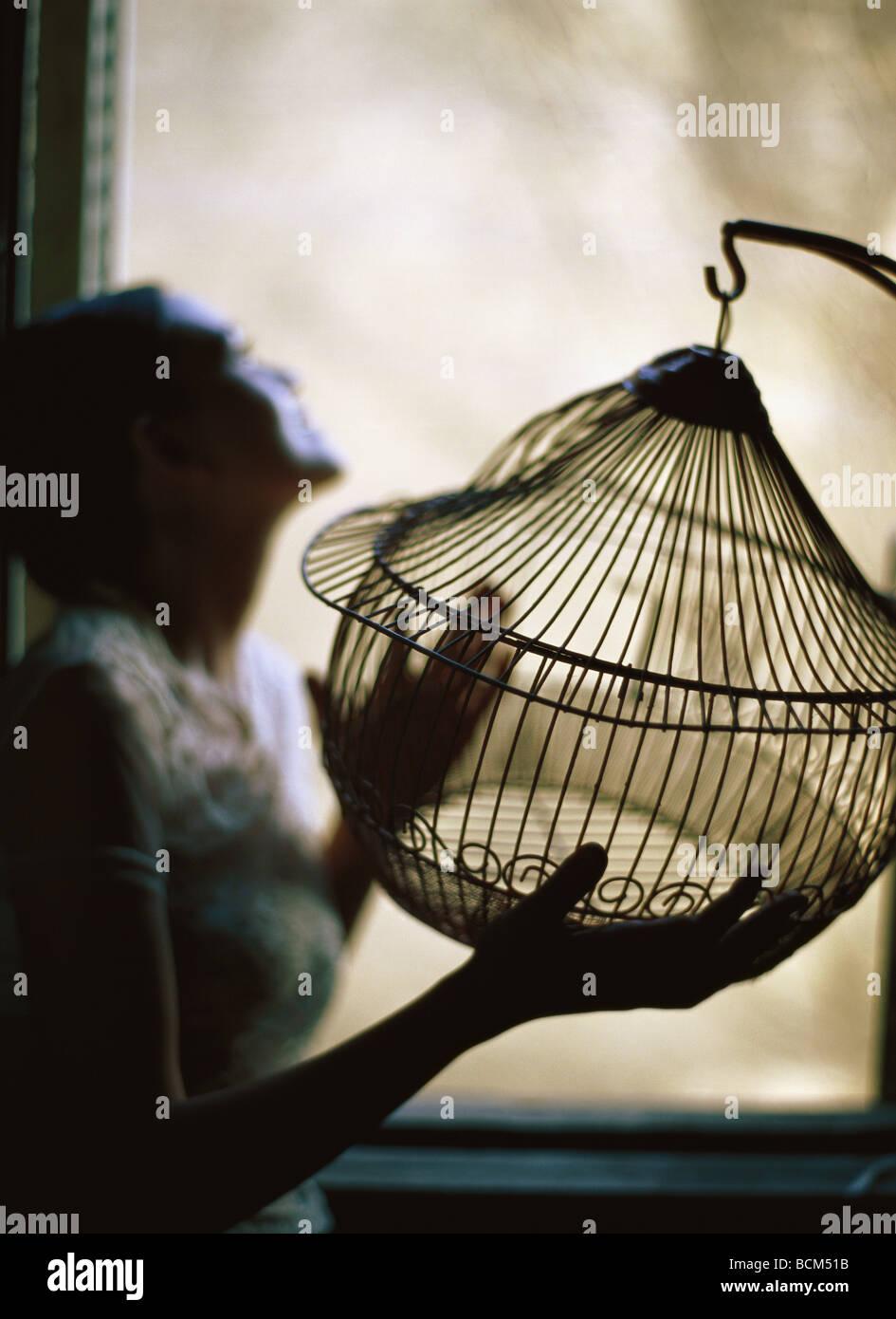 Woman standing beside window, holding empty birdcage - Stock Image