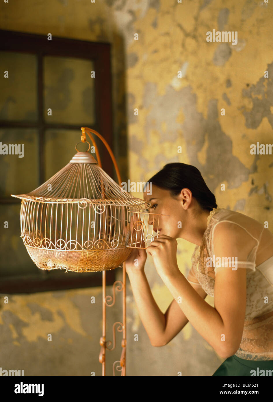 Woman looking inside empty birdcage, side view - Stock Image
