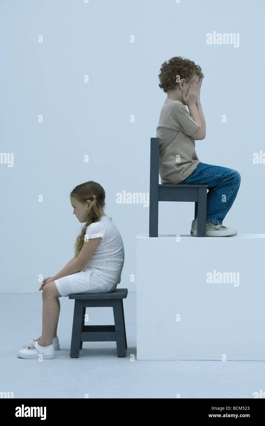 Boy and girl sitting back to back on chairs, boy elevated on ledge, covering face with hands - Stock Image