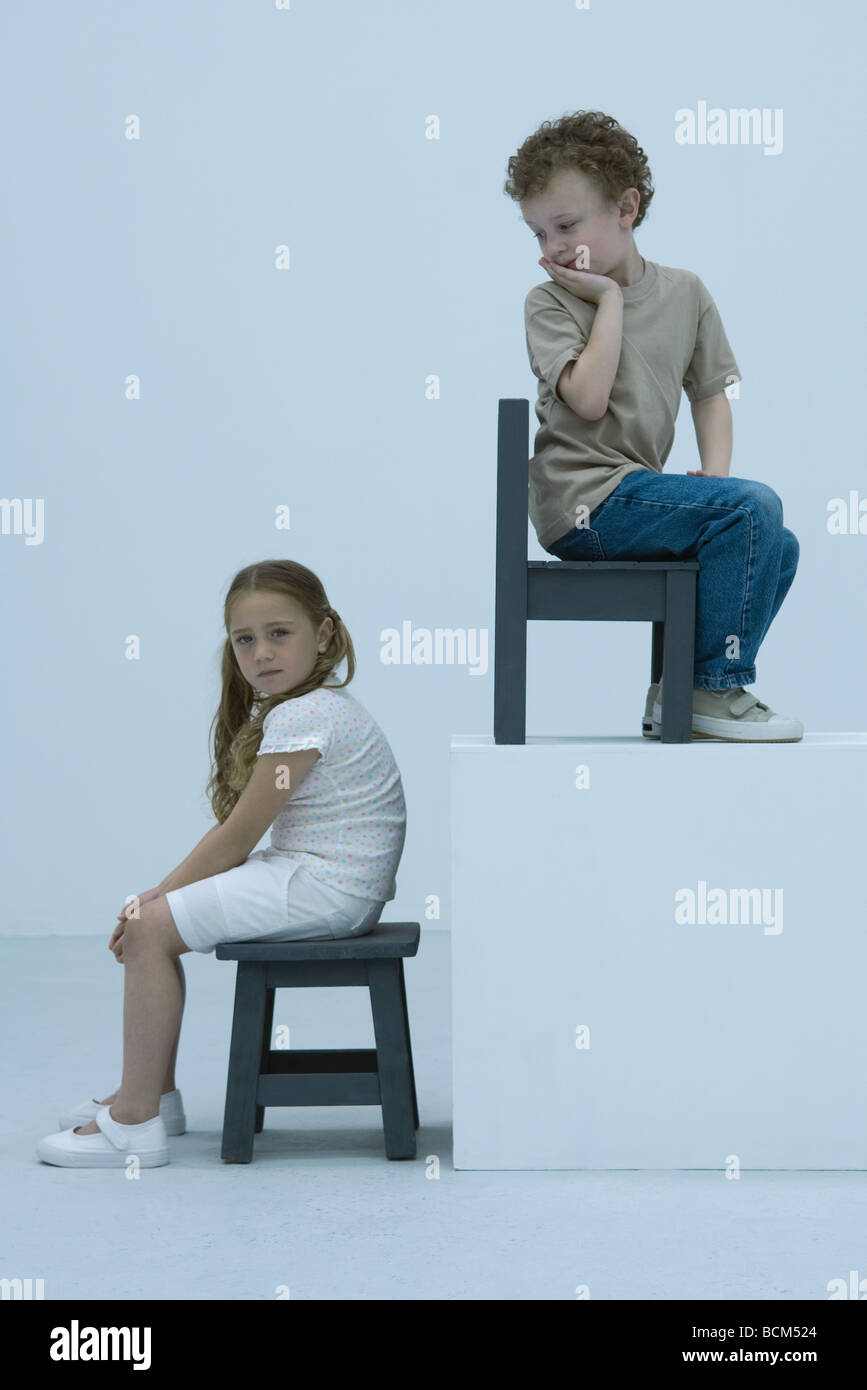 Girl sitting on stool, looking at camera, boy elevated on ledge behind, looking over shoulder at girl - Stock Image