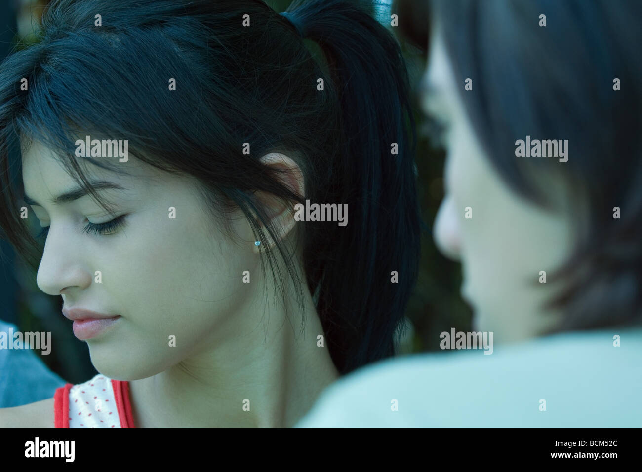 Young woman turning head away from teen boy, cropped view - Stock Image
