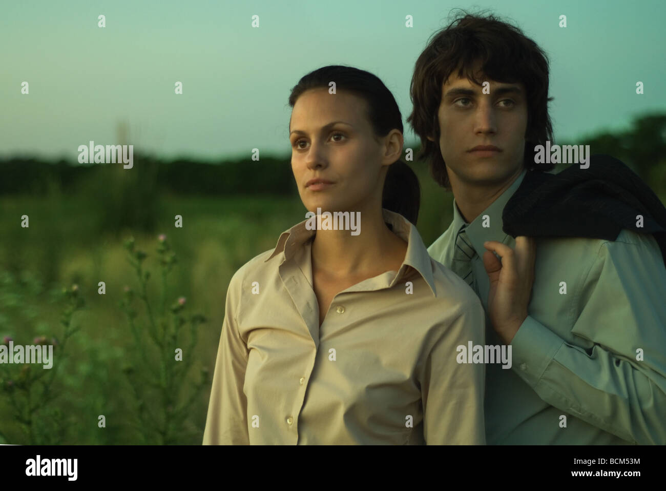 Couple standing together in field at dusk, close-up - Stock Image