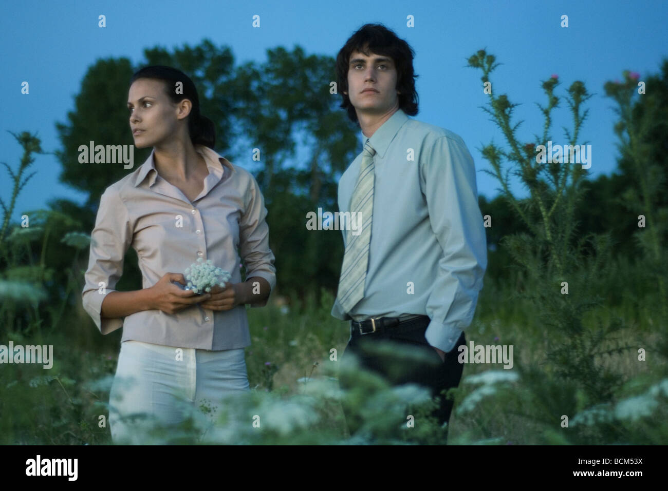 Couple standing in field, looking away, woman holding wildflowers - Stock Image
