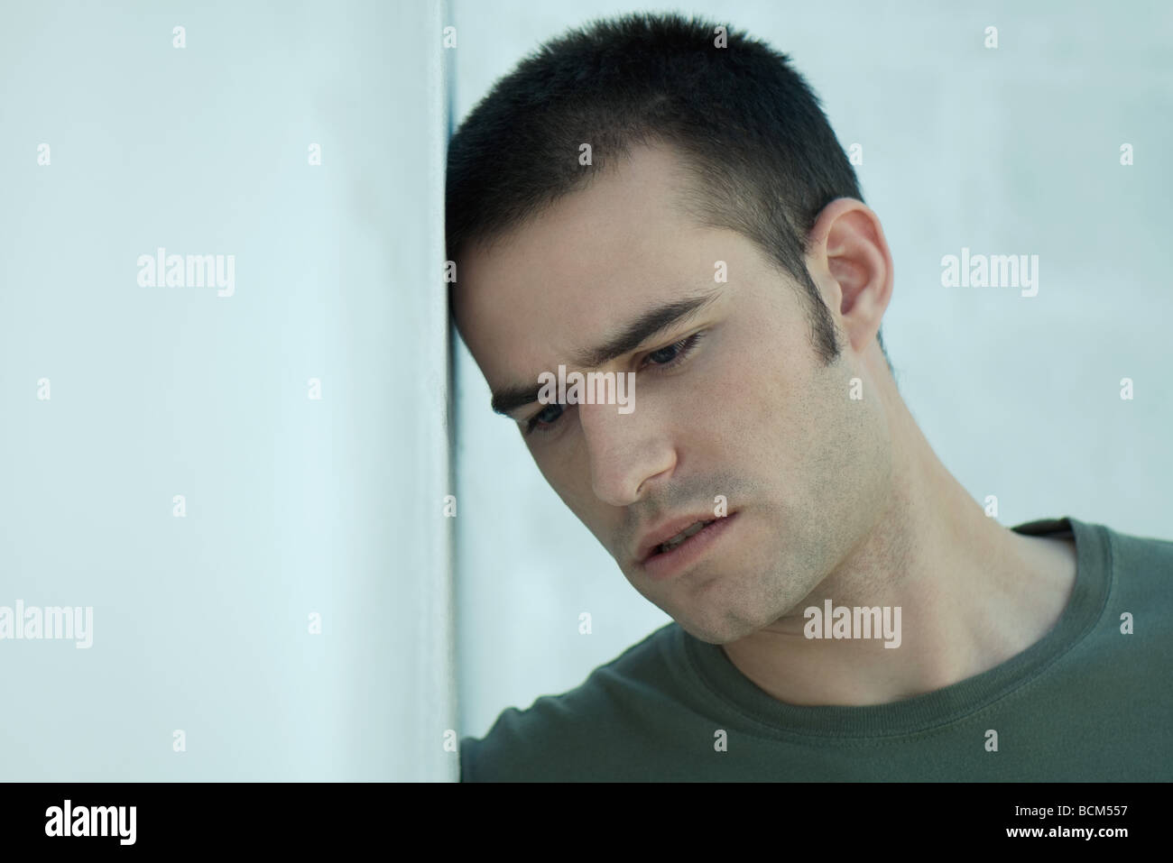 Man leaning head against wall, furrowing brow - Stock Image