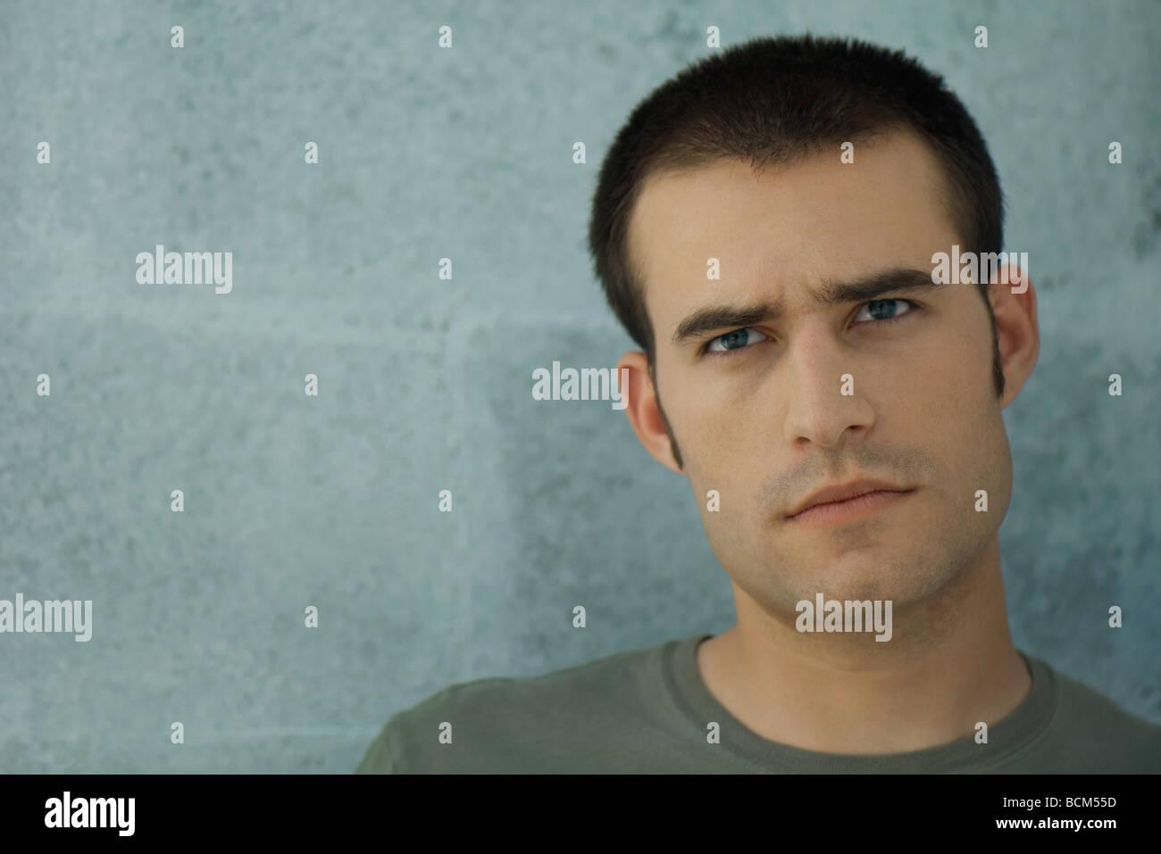 Man furrowing brow, frowning - Stock Image