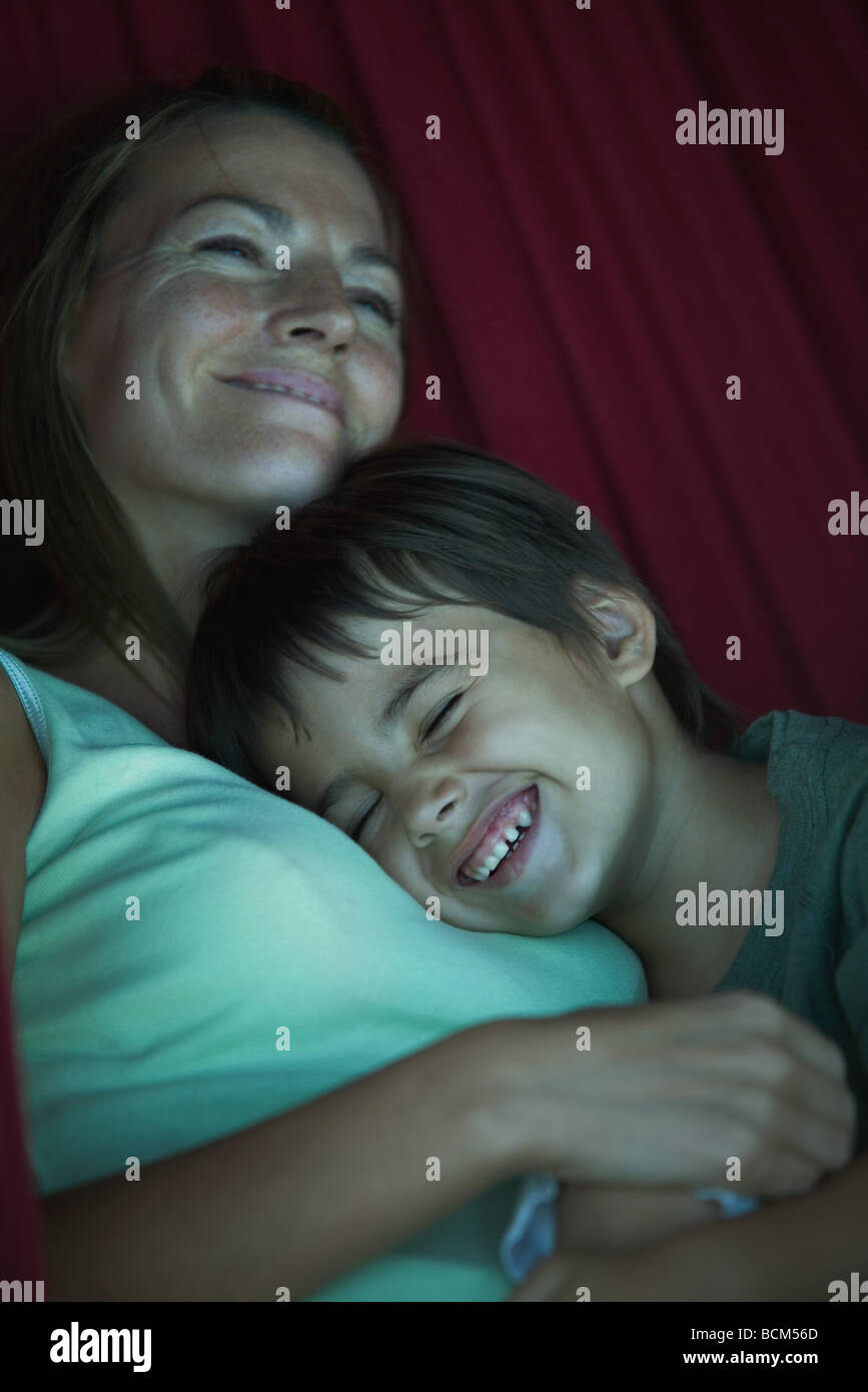 Mother and son reclining together, smiling - Stock Image